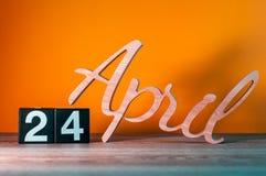 24 avril Jour 24 du mois, calendrier en bois quotidien sur la table avec le fond orange Concept de printemps Photographie stock libre de droits