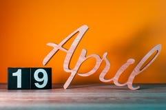 19 avril Jour 19 du mois, calendrier en bois quotidien sur la table avec le fond orange Concept de printemps Images libres de droits