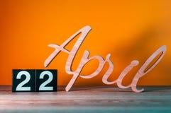 22 avril Jour 22 du mois, calendrier en bois quotidien sur la table avec le fond orange Concept de printemps Photographie stock