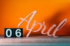 6 avril Jour 6 du mois, calendrier en bois quotidien sur la table avec le fond orange Concept de printemps Photo stock