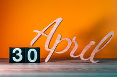 30 avril Jour 30 du mois, calendrier en bois quotidien sur la table avec le fond orange Concept de printemps Photo libre de droits