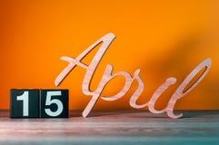 15 avril Jour 15 du mois, calendrier en bois quotidien sur la table avec le fond orange Concept de printemps Images libres de droits