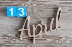 13 avril Jour 13 du mois d'avril, calendrier de couleur sur le fond en bois Le printemps… a monté des feuilles, fond naturel Photos libres de droits