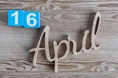 16 avril Jour 16 du mois d'avril, calendrier de couleur sur le fond en bois Le printemps… a monté des feuilles, fond naturel Images libres de droits
