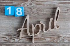 18 avril Jour 18 du mois d'avril, calendrier de couleur sur le fond en bois Le printemps… a monté des feuilles, fond naturel Images libres de droits