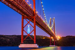 25 avril pont et Christ la statue de roi à Lisbonne Portugal au coucher du soleil Photographie stock libre de droits