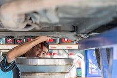 Avrinning för bilmekaniker den gamla smörjmedelmotoroljan arkivbild