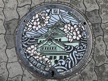Avrinningräkning med den Osaka slottsymbolen på Osaka, Japan royaltyfri bild