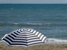 Avrivet paraply på stranden royaltyfri bild