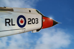 Avro Arrow. A white Canadian Avro Arrow jet interceptor glints in the sun as it breaks out of the clouds, at the speed of sound, into a clear blue sky stock photography