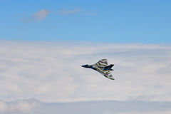 Avro Vulcan Bomber. Avro Vulcan aircraft banking to the left against blue sky and cloud stock photos