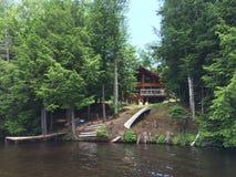 Avskild kabin på sjön Arkivbild
