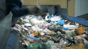 Avskrädeåtervinningsanläggning En person i handskar väljer icke- återanvändbart avfall från en rörande linje på en förlorad sorte arkivfilmer