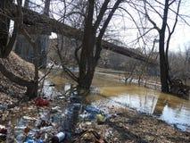 Avskräde flaskor, gyttja på våren Miljö- katastrof royaltyfri bild