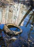 Avskräde, gammalt gummihjul och reflexion av höghuset i vattnet Royaltyfri Bild