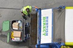 Avskrädeman som laddar en avskrädelastbil Royaltyfri Bild