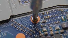 Avskruvning av skruven Rotera skruven på elektroniskt tryckströmkretsbräde stock video