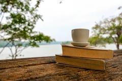 Avslappnande ögonblick, bok- och kaffekopp på den wood tabellen Koppla av tid på feriebegreppslopp, arkivbilder
