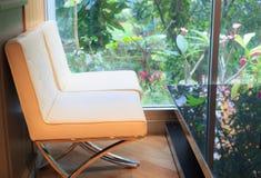 Avslappnande ögonblick i kaffekafét, mjuka kräm- lädersoffor med den svarta glass tabellen bredvid stort fönster med grönt dekora Arkivbilder