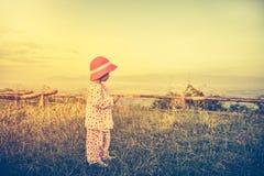Avslappnande det fria för asiatiskt barn, lopp på semester Inte gör de ser smaskiga Arkivfoto