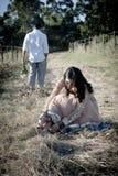Avslappnande det fria för unga härliga indiska par i fält Fotografering för Bildbyråer