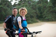 Avslappnande det fria för gladlynta par med cyklar Fotografering för Bildbyråer