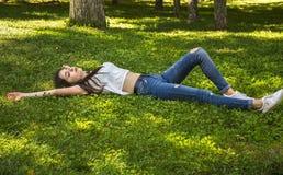 Avslappnande flicka som ligger på gräset royaltyfria foton