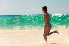 Avslappnande flickaspring på en strand royaltyfria bilder