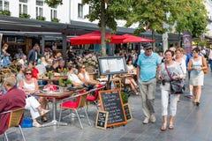 Avslappnande folk på terrasser som är i stadens centrum i staden Antwerp, Belgien Arkivfoto