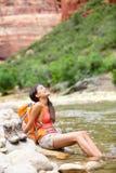 Avslappnande fotvandrarekvinna som vilar fot, i att fotvandra för flod Arkivfoton