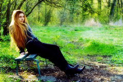 avslappnande fundersam kvinna för härlig bänkpark Royaltyfri Foto