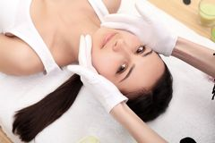 Avslappnande härlig kvinna som har en massage för hennes hud på en framsida i den horisontalskönhetsalongen - arkivfoto