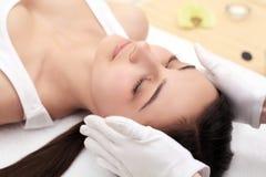 Avslappnande härlig kvinna som har en massage för hennes hud på en framsida i den horisontalskönhetsalongen - fotografering för bildbyråer