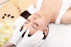 Avslappnande härlig kvinna som har en massage för hennes hud på en framsida i den horisontalskönhetsalongen - royaltyfria bilder