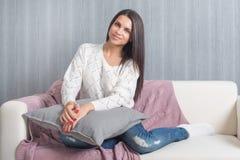 Avslappnande hemmastatt, komfort gullig ung kvinna som ler och att koppla av på den vita soffan, soffa hemma arkivfoto