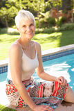 avslappnande hög kvinna för trädgårds- pöl Royaltyfri Fotografi