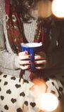 Avslappnande innehav för kvinna en råna av kaffe/te/varm choklad Arkivbild