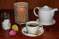 Avslappnande kopp te med tekannan, stearinljuset och blommor royaltyfria bilder