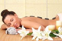 avslappnande kvinna med stenar på henne tillbaka i en Spa Royaltyfri Foto