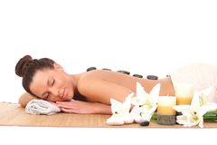 avslappnande kvinna med stenar på henne tillbaka i en Spa Royaltyfria Bilder