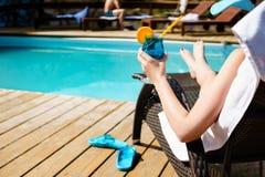 Avslappnande kvinna nära lyxig simbassäng Royaltyfri Bild