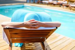 Avslappnande kvinna nära lyxig simbassäng Royaltyfri Foto