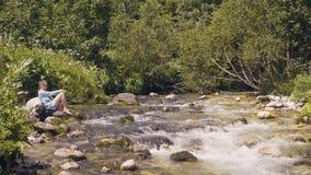 Avslappnande kvinna på stenig flodkust medan sommarvandring filialer torkar wild för flodstrand för floden för naturen för berg f lager videofilmer