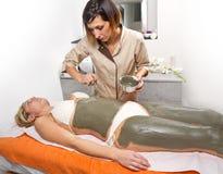 Avslappnande kvinna som ligger på en massagetabell som mottar treatmen för en gyttja Royaltyfria Bilder