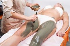 Avslappnande kvinna som ligger på en massagetabell som mottar treatmen för en gyttja Arkivfoto