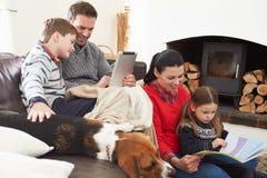 Avslappnande läsebok för familj och använda den Digital minnestavlan Royaltyfri Bild