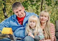 Avslappnande lycklig ung familj utomhus Royaltyfria Bilder