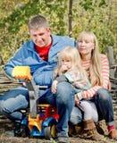 Avslappnande lycklig ung familj utomhus Arkivbilder