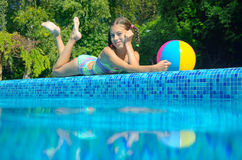 Avslappnande near pöl för flicka som är undervattens- och ovanför sikt Royaltyfri Foto