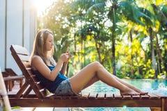 Avslappnande near simbassäng för lycklig smartphonekvinna som lyssnar med earbuds till tryckning av musik Härlig flicka som använ fotografering för bildbyråer